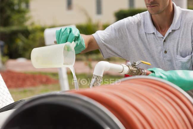 Tecnico di controllo dei parassiti che mescola sostanze chimiche con acqua nel serbatoio chimico — Foto stock