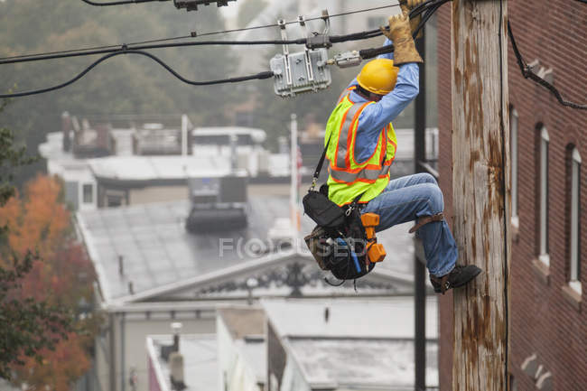 Cable lineman holding onto pole while using lineman spikes to adjust tension — Stock Photo