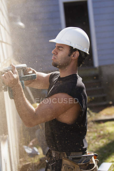 Hispanic carpenter trimming house siding for installation of new deck — Stock Photo