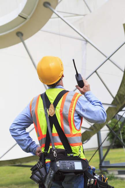 Інженери зв'язку використовують радіоприймач на супутниковій антені. — стокове фото