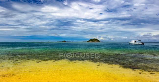 Boot ankert vor der Küste der Insel Malolo im klaren, ruhigen Wasser des Südpazifiks; Insel Malolo, Fidschi — Stockfoto