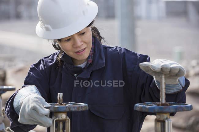 Ingeniera de potencia femenina ajustando válvulas de agua en planta de energía - foto de stock