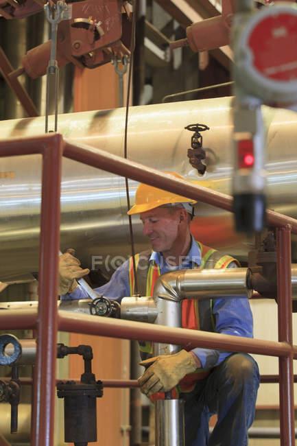 Ingenieur im Elektrizitätswerk überprüft manuelles Ventil in Kondensatorrohrleitungen — Stockfoto