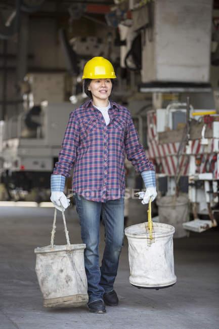 Female power engineer preparing canvas buckets in service garage near equipment truck — Stock Photo