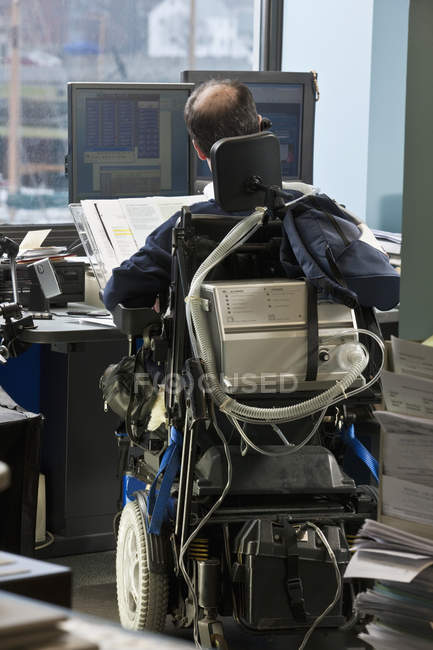 Businessman with Duchenne muscular dystrophy in a motorized wheelchair working in an office — Stockfoto