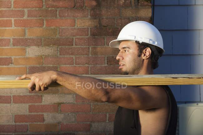Hispanic carpenter carrying pressure treated lumber at house site — Stock Photo