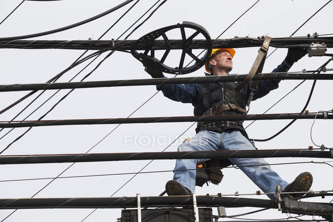 Communications worker examining cables on power pole — Stock Photo