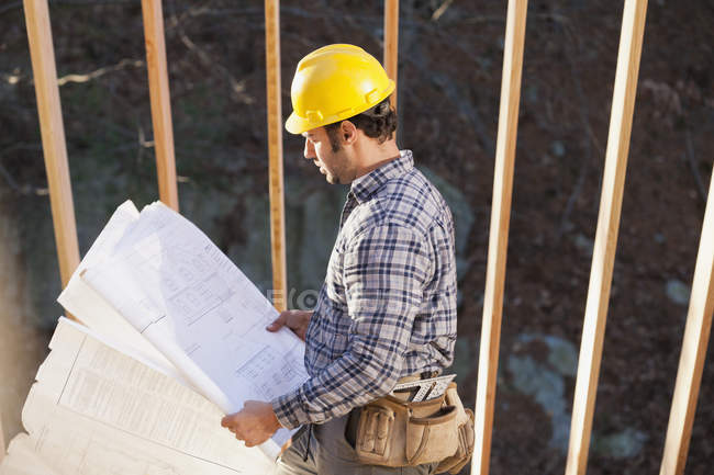 Carpenter reading house plans for house construction — Stock Photo