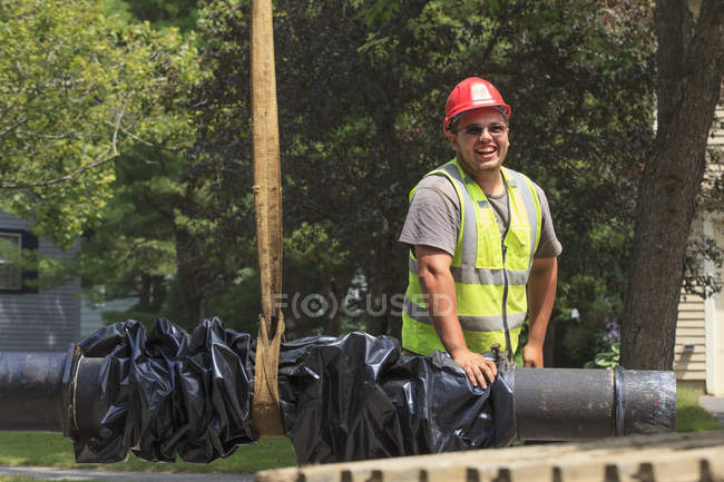 Construction worker guiding water main into place — Stock Photo