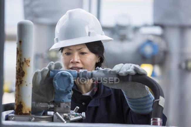 Ingeniera de potencia femenina verificando transductor en central eléctrica - foto de stock