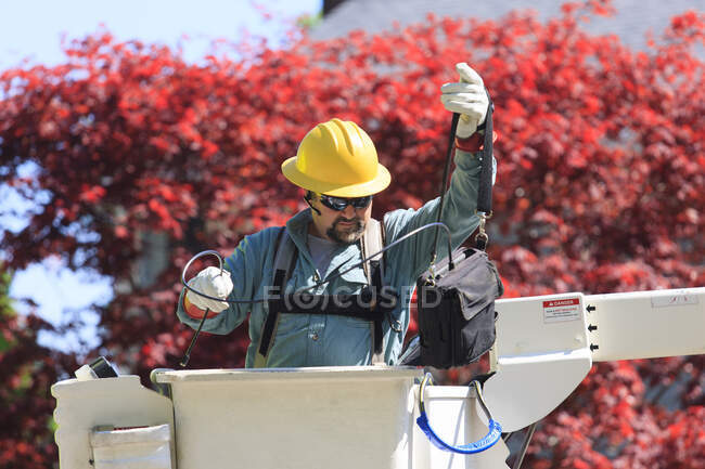 Power engineer in lift bucket working with power lines — Stock Photo