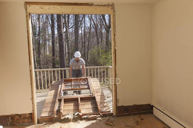 Spanisch Tischler entfernt neu geschnittene Tür Zugang zu Deck zu Hause — Stockfoto