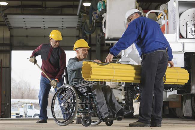 Контроль за обслуговуванням керує людиною з травмами спинного мозку, яка готується завантажувати екранування на вантажний автомобіль — стокове фото