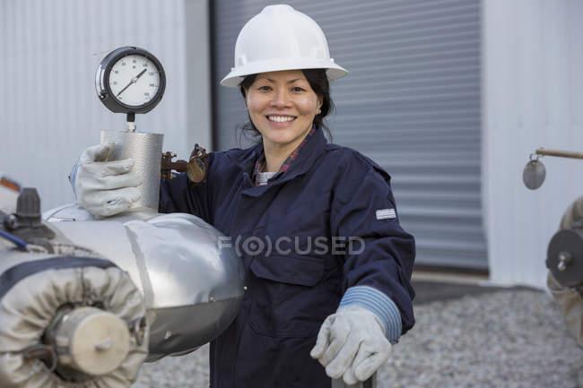 Retrato del ingeniero de potencia femenino con sensor de presión en la central eléctrica - foto de stock