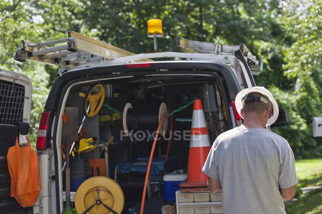 Instalador de cable preparando equipo en camión para visitar el sitio - foto de stock