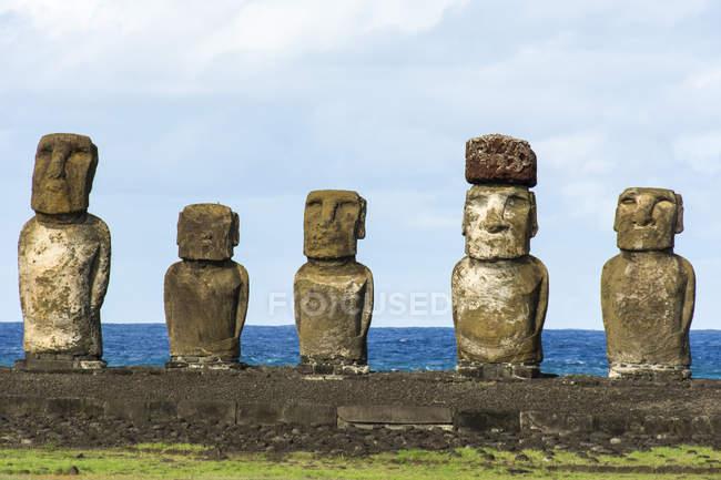 Cinq moais sur leur plateforme à la lumière du matin avec l'océan en arrière-plan ; Île de Pâques, Chili — Photo de stock