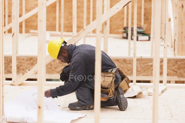 Tischler überprüft Baupläne vor Ort — Stockfoto