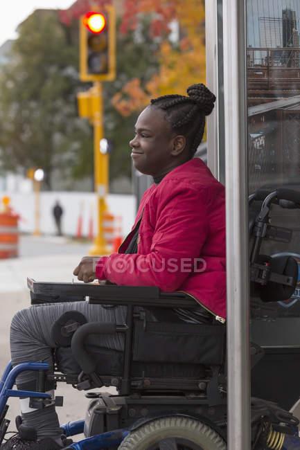 Подросток с церебральным параличом на автобусной остановке — стоковое фото