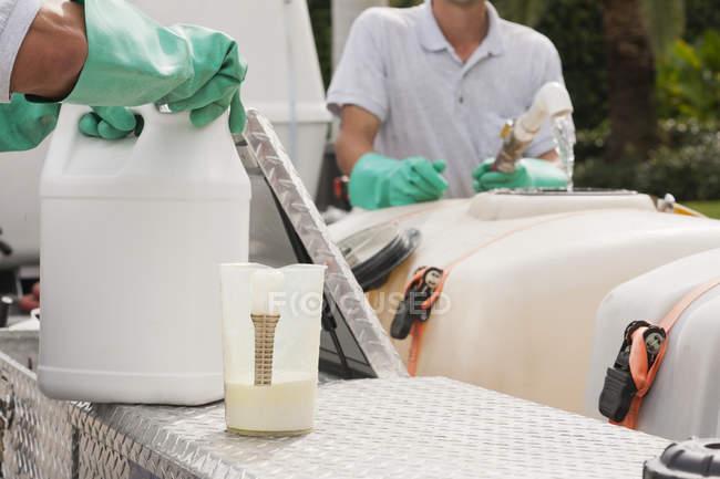 Tecnici di lotta contro i parassiti mescolando sostanze chimiche al serbatoio chimico nel camion di servizio — Foto stock