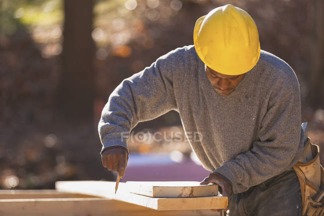 Carpenter marking bevel cuts on rafter — Stock Photo