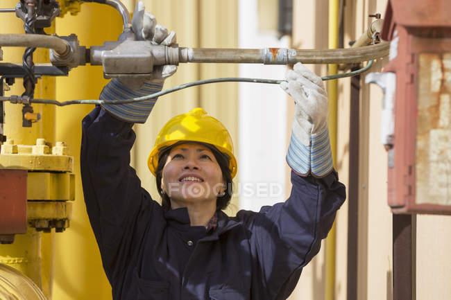 Ingeniera de potencia femenina verificando sensores de línea de combustible en planta eléctrica - foto de stock