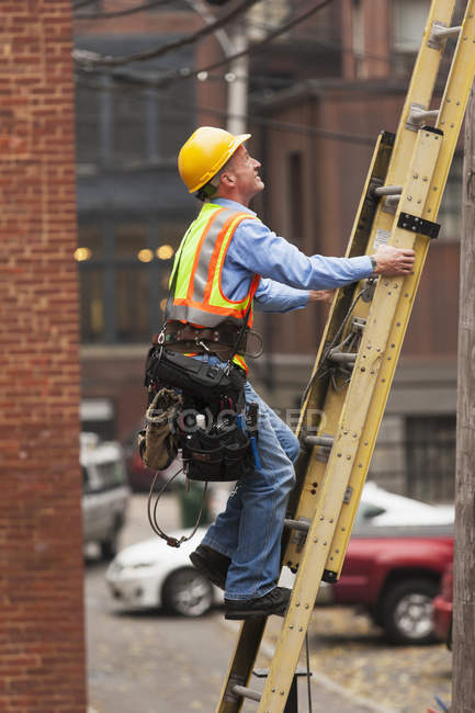 Cable lineman climbing up a ladder on city building — Stock Photo