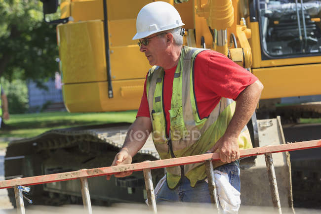 Construction worker on site carrying ladder — Stock Photo