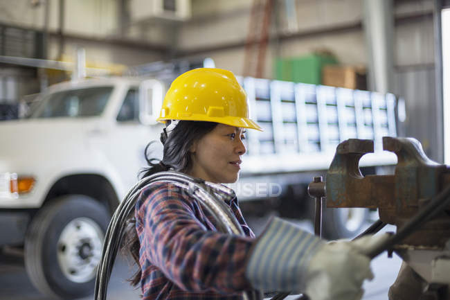 Female power engineer with power cable in service garage — Stock Photo
