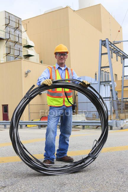 Engineer at electric power plant carrying coil of wire at storage area — Stock Photo