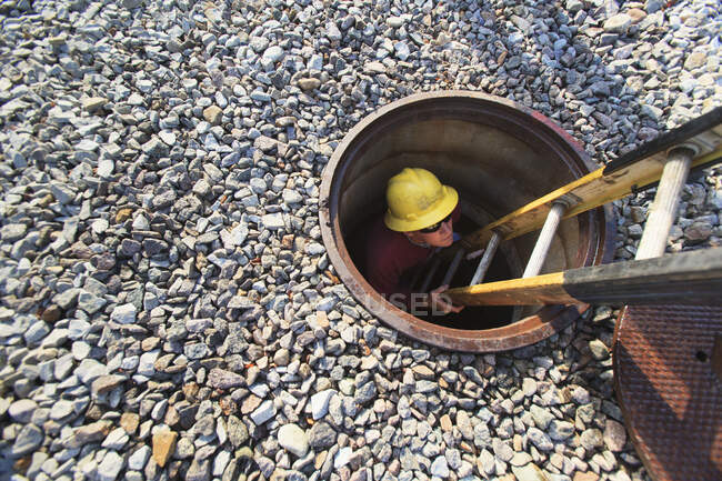 Power engineer inside climbing ladder in manhole at high voltage power distribution station — Stock Photo