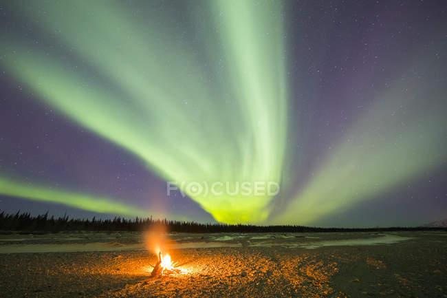 Aurora borealis над костром на Джарвис-Крик в Дельта Джанкшн, Аляска, Соединенные Штаты Америки — стоковое фото