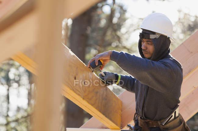 Carpenter measuring a laminated beam — Stock Photo