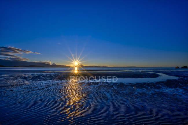 Coucher de soleil sur la baie de Tasman, illuminant le sable humide sur le rivage de Pohara Beach ; Nelson, île du Sud, Nouvelle-Zélande — Photo de stock