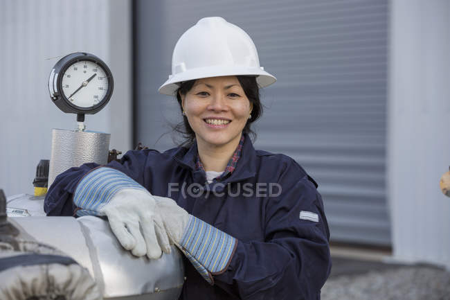 Portrait of female power engineer with pressure sensor at power station — Stock Photo