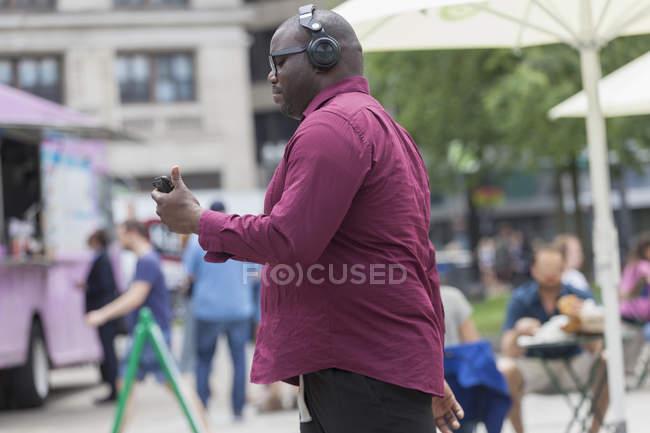 Hombre con TDAH usando un teléfono móvil en la calle de la ciudad - foto de stock