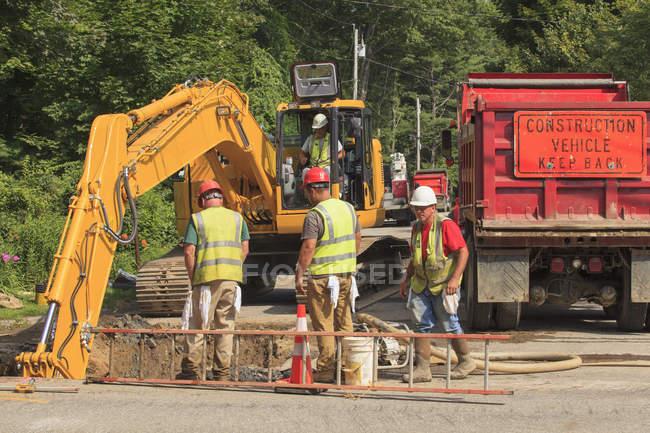 Строители наблюдают, как экскаваторы рыли отверстие на водопроводной магистрали — стоковое фото