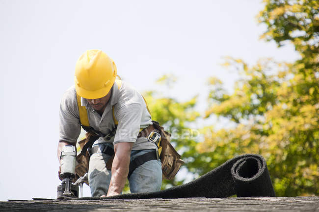 Roofer working on shingling a new roof — Stock Photo