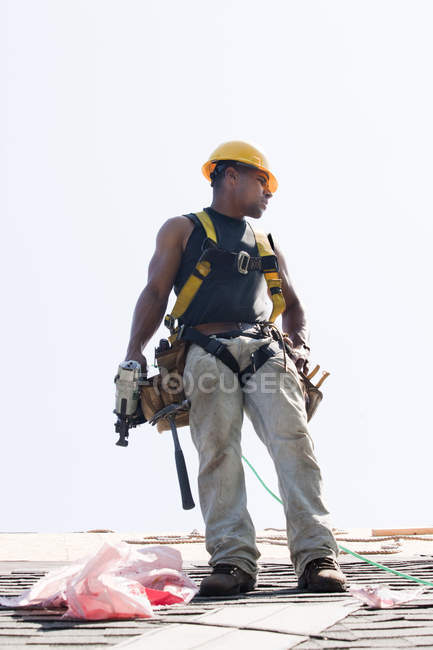 Roofer with nail gun putting shingles on roof of new home — Stock Photo