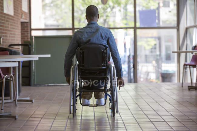 Hombre que tenía meningitis espinal en una silla de ruedas dirigiéndose a un ascensor de escaleras en una oficina - foto de stock