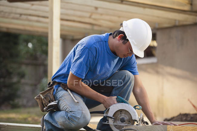 Carpenter cutting deck joist with a circular saw — Stock Photo