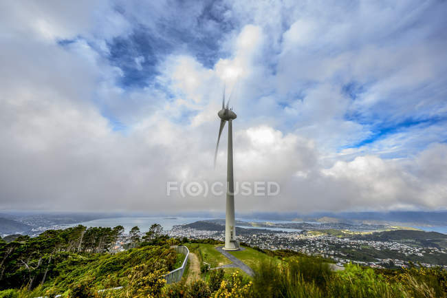 Wind turbine at high elevation with a view of a cityscape of Wellington and coastline of the North Island of New Zealand below; Wellington, North Island, New Zealand — Stock Photo