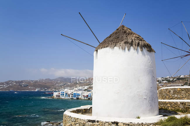 Mediterranean coastline of Greece with white buildings and windmills along the water edge; Greece — Stock Photo