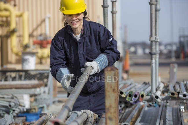 Female power engineer sorting through scaffolding at power plant — Stock Photo
