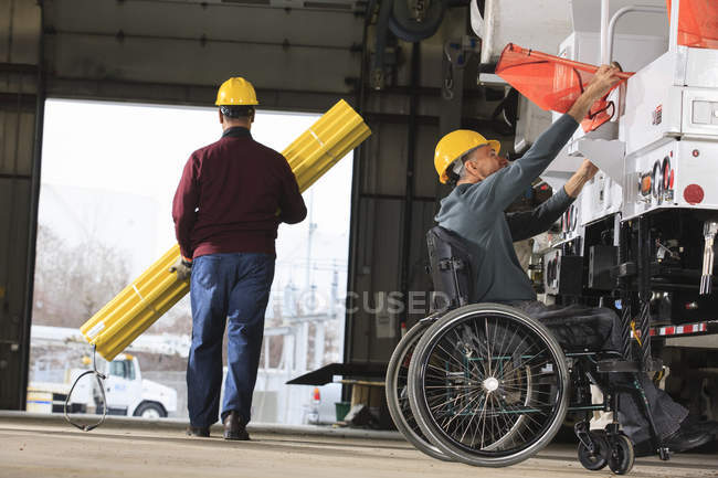 Maintenance supervisor with a spinal cord injury in utility garage and loading new truck with supplies one man carrying hole shielding — Stock Photo