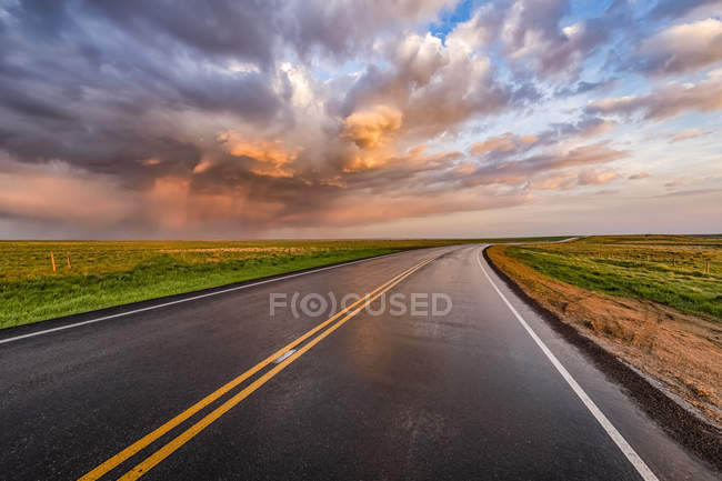 Winding country road at sunset; Val Marie, Saskatchewan, Canada — Stock Photo