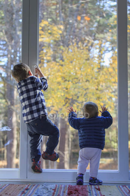 Rear view of a brother and his baby sister climbing on the door — Stockfoto