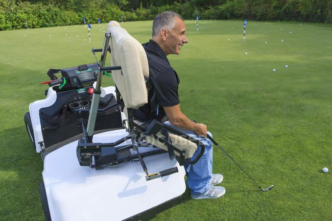 Mann mit Querschnittslähmung in adaptivem Cart auf Golf Putting Green — Stockfoto