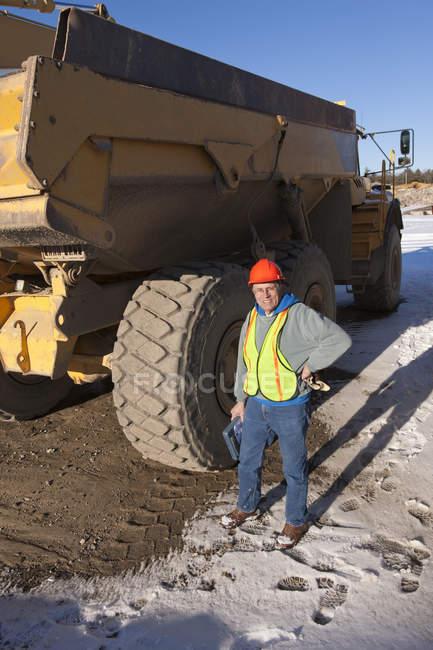 Инженер во время осмотра землеройщиков на строительной площадке — стоковое фото