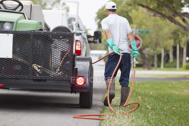 Técnico de control de plagas con pistola de pulverización de alta presión y manguera en su camión. - foto de stock