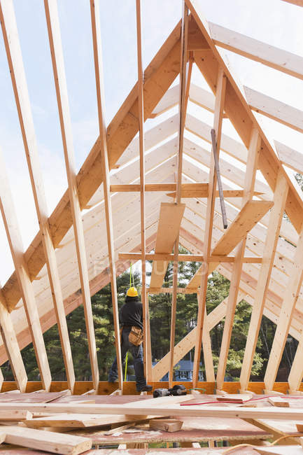 Carpenter standing on joist of roof under construction — Stock Photo